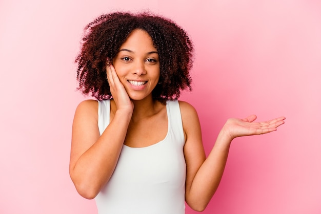 Young african american mixed race woman isolated holds copy space on a palm, keep hand over cheek. amazed and delighted.