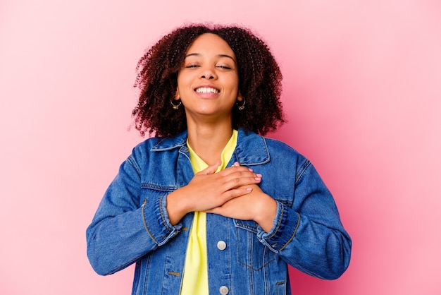 Young african american mixed race woman isolated laughing keeping hands on heart, concept of happiness.
