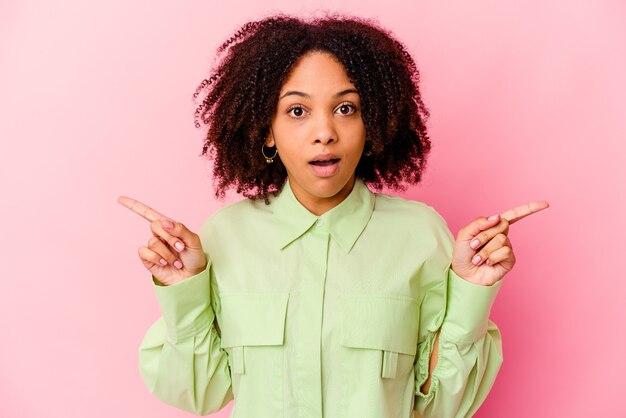 Молодая афро-американская женщина смешанной расы изолирована, указывая на разные копии пространства, выбирая одно из них, показывая пальцем.