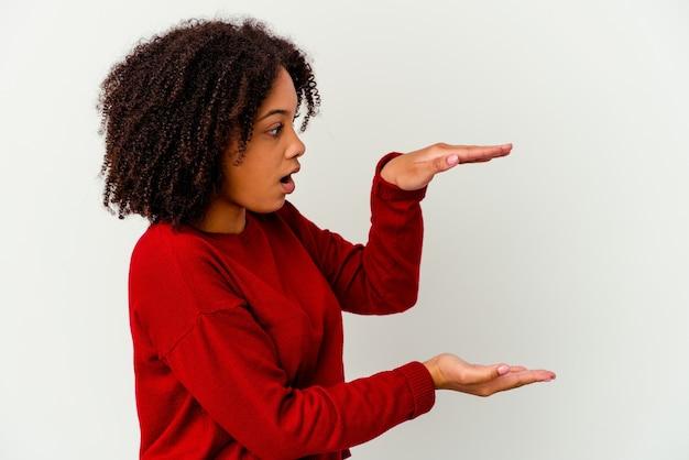 Молодая афро-американская женщина смешанной расы изолирована шокирована и поражена, держа копию пространства между руками.