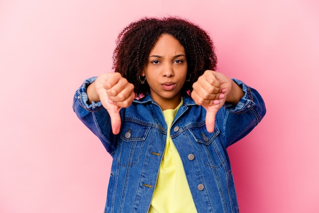 Young african american mixed race woman isolated showing thumb down and expressing dislike.