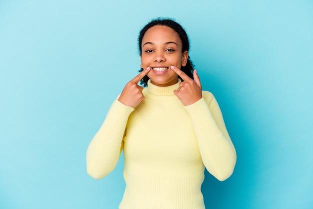 若いアフリカ系アメリカ人の混血の女性は、口に指を指して、笑顔を分離しました。