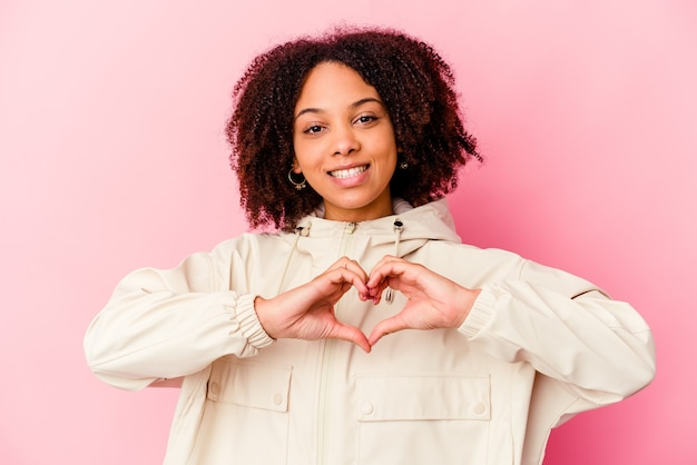 Young african american mixed race woman isolated smiling and showing a heart shape with hands.