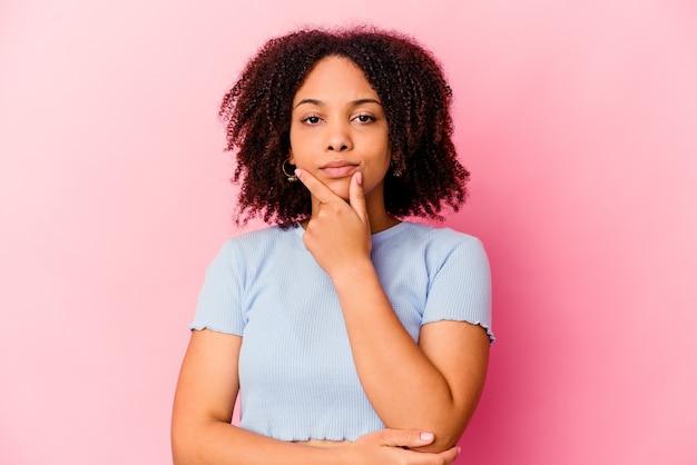 Молодая афро-американская женщина смешанной расы изолировала подозрительную, неуверенную, изучая вас.