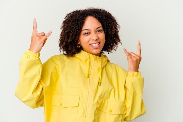 革命の概念として角のジェスチャーを示す若いアフリカ系アメリカ人の混血の女性。