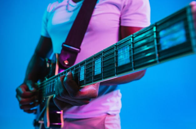 Young african-american musician playing the guitar like a rockstar on blue studio background in neon light. concept of music, hobby. joyful  guy improvising. retro colorful portrait.