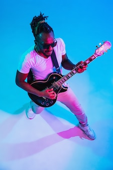 Young african-american musician playing the guitar like a rockstar on blue wall in neon light.