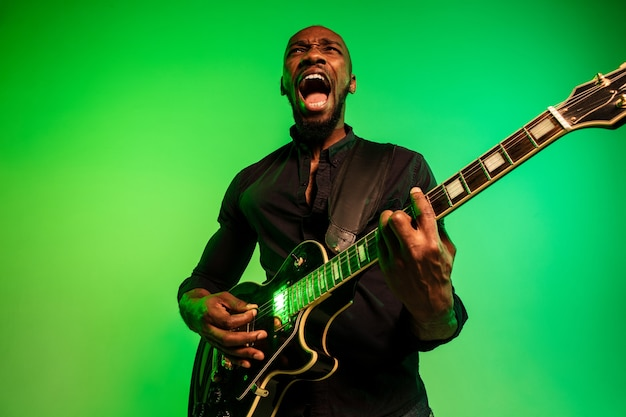 Young african-american musician playing the guitar like a rockstar on gradient green-yellow background.