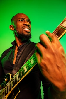 Young african-american musician playing the guitar like a rockstar on gradient green-yellow wall.