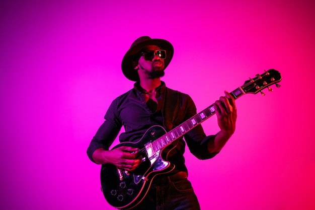 Young african-american musician playing the guitar like a rockstar on gradient purple-pink background in neon light. concept of music, hobby. joyful  guy improvising.