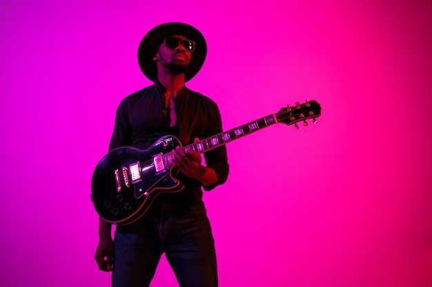 Young african-american musician playing the guitar like a rockstar on gradient purple-pink background in neon light.