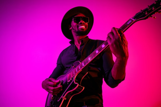 Young african-american musician playing the guitar like a rockstar on gradient purple-pink wall in neon light