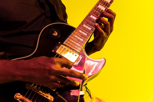 Young african-american musician playing the guitar like a rockstar on yellow background in neon light.