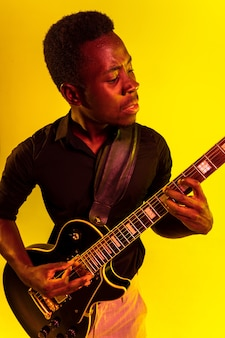 Young african-american musician playing the guitar like a rockstar on yellow wall in neon light.