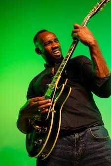 Молодой афро-американский музыкант играет на гитаре как рок-звезда на градиентном зелено-желтом фоне. понятие музыки, хобби, фестиваля, пленэра. веселый парень импровизирует, поет песню.