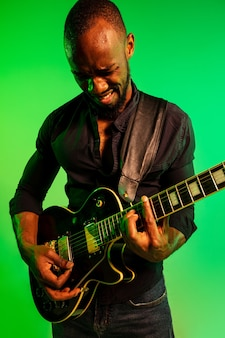 그라데이션 녹색 노란색 배경에 록 스타처럼 기타를 연주하는 젊은 아프리카 계 미국인 음악가. 음악, 취미, 축제, 야외의 개념. 즉흥적으로 노래하는 즐거운 남자.