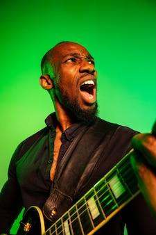 그라데이션 녹색 노란색 배경에 록 스타처럼 기타를 연주하는 젊은 아프리카 계 미국인 음악가.