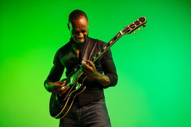 緑黄色のグラデーションの背景でロックスターのようにギターを弾く若いアフリカ系アメリカ人のミュージシャン。