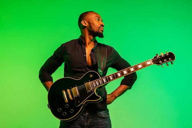 그라데이션 녹색 노란색에 록 스타처럼 기타를 연주하는 젊은 아프리카 계 미국인 음악가