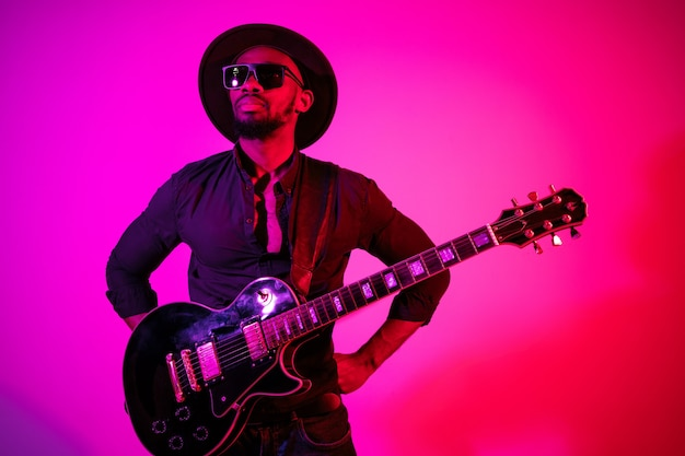 ネオンの光の中でグラデーション紫ピンクの背景にロックスターのようにギターを弾く若いアフリカ系アメリカ人のミュージシャン。