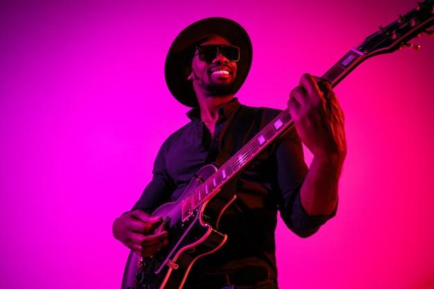 Молодой афро-американский музыкант играет на гитаре как рок-звезда на градиентной фиолетово-розовой стене в неоновом свете