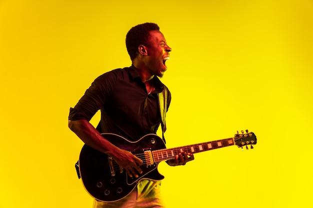 네온 불빛 아래 노란색 배경에서 록스타처럼 기타를 연주하는 젊은 아프리카계 미국인 음악가. 음악, 취미, 축제, 야외의 개념. 즉흥적으로 노래를 부르는 유쾌한 매력적인 남자.