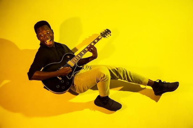 네온 불빛에 노란색 바탕에 록 스타처럼 기타를 연주하는 젊은 아프리카 계 미국인 음악가.