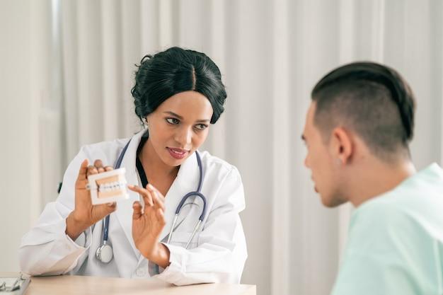 若いアフリカ系アメリカ人または幸せな顔の笑顔で義歯を保持している黒人の歯科医の女性
