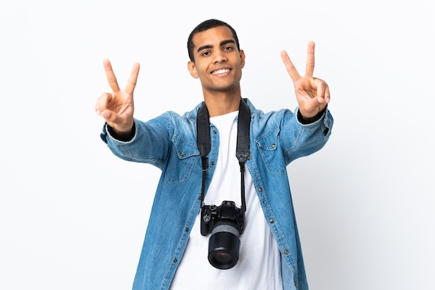 Young african american photographer man over isolated white background smiling and showing victory sign