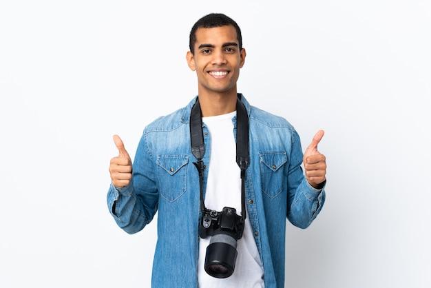 親指のジェスチャーを与える孤立した白い壁を越えて若いアフリカ系アメリカ人写真家男