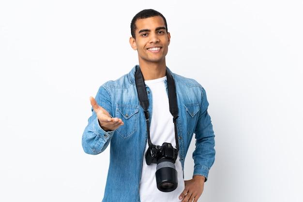 取引後の孤立した白い壁のハンドシェークの若いアフリカ系アメリカ人カメラマン男