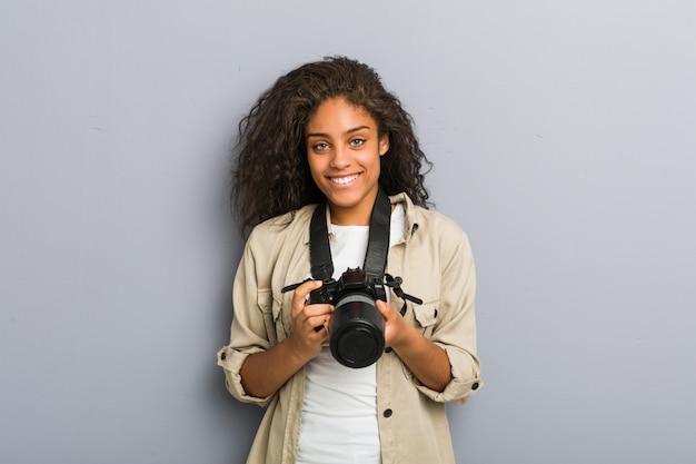Молодая женщина фотографа афроамериканца держа камеру счастливый, усмехаться и жизнерадостный.