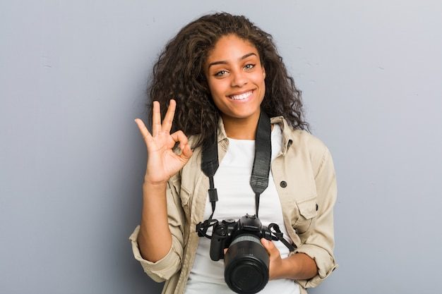 Young african american photographer woman holding a camera cheerful and confident showing ok gesture.