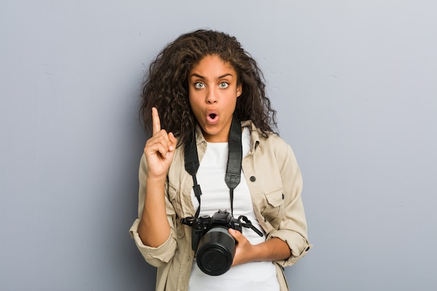 Young african american photographer woman holding a camera having some great idea, concept of creativity.