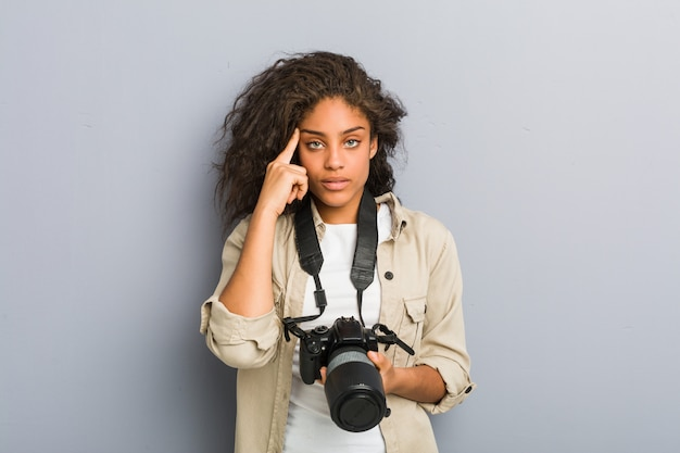 Young african american photographer woman holding a camera pointing his temple with finger, thinking, focused on a task.