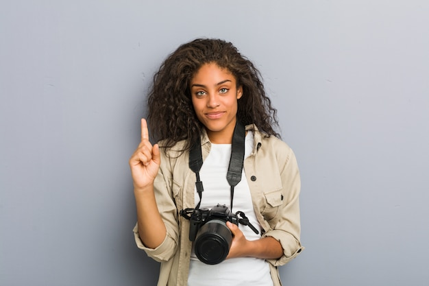 Young african american photographer woman holding a camera showing number one with finger.