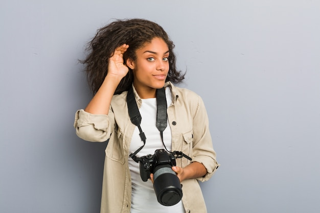 Young african american photographer woman holding a camera trying to listening a gossip.