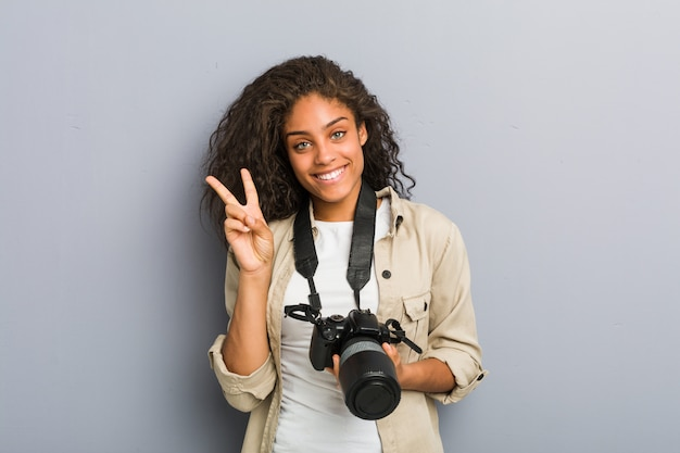 Young african american photographer woman with camera showing victory sign and smiling broadly.