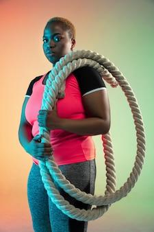 Allenamento del giovane modello femminile afro-americano plus size sulla parete sfumata in luce al neon.