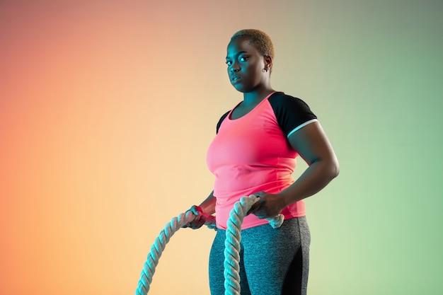 네온 불빛에 그라데이션 벽에 젊은 아프리카 계 미국인 플러스 크기 여성 모델의 교육.