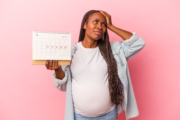 Young african american pregnant woman holding calendar isolated on pink background being shocked, she has remembered important meeting.