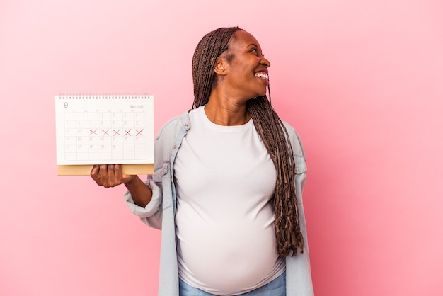Young african american pregnant woman holding calendar isolated on pink background looks aside smiling, cheerful and pleasant.