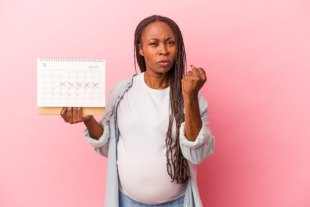 Young african american pregnant woman holding calendar isolated on pink background showing fist to camera, aggressive facial expression.