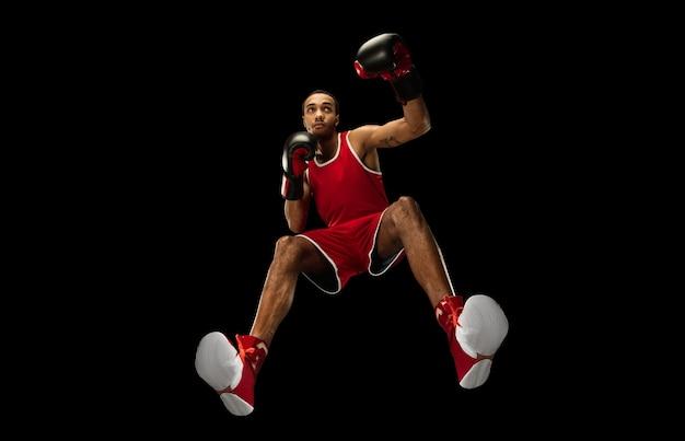 Молодой афро-американский профессиональный боксер в действии, движение, изолированное на черной стене, взгляд снизу. понятие спорта, движения, энергии и динамичного, здорового образа жизни. обучение, практика.