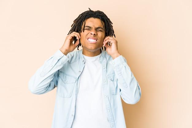 若いアフリカ系アメリカ人のラスター男が耳を指で覆い、ストレスのたまった大声で必死になって。