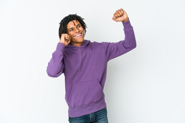 Молодой афро-американский раста-мужчина танцует и веселится.