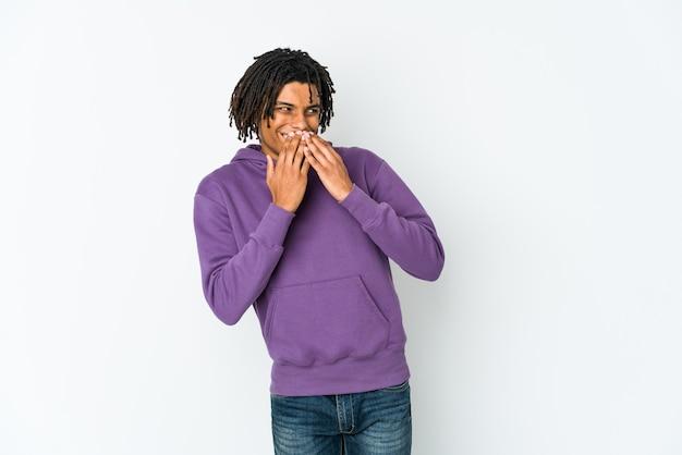 若いアフリカ系アメリカ人のラスター男が何かで笑いながら、手で口を覆っています。