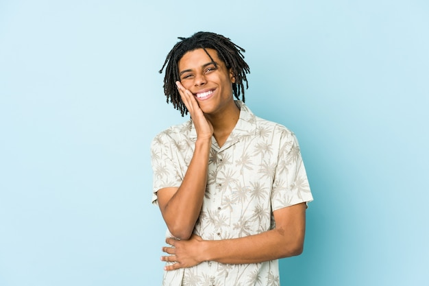 若いアフリカ系アメリカ人のラスター男は幸せそうに笑い、胃に手をつないで楽しんでいます。