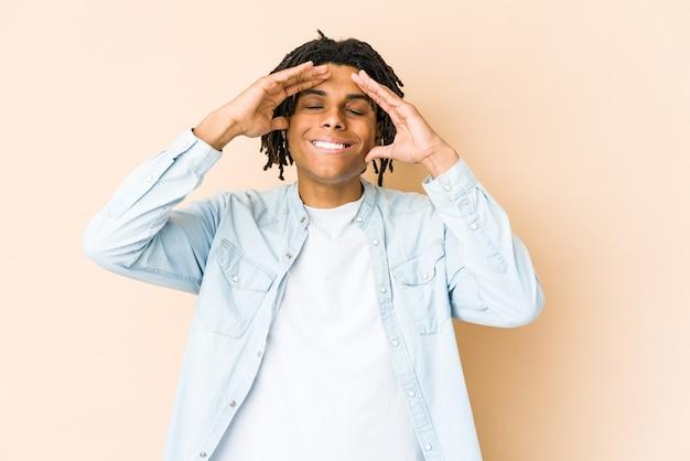 Молодой афро-американский раста-мужчина радостно смеется, держась за голову. концепция счастья.