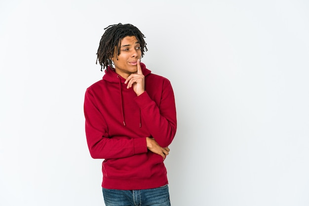 Young african american rasta man looking sideways with doubtful and skeptical expression.